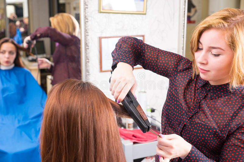 Stylist Using Flat Iron on Hair of Brunette Client stock photography