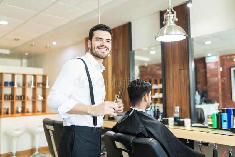 Stylista ono Uśmiecha się Podczas gdy Przygotowywający klienta ` s włosy W fryzjera męskiego sklepie fotografia stock