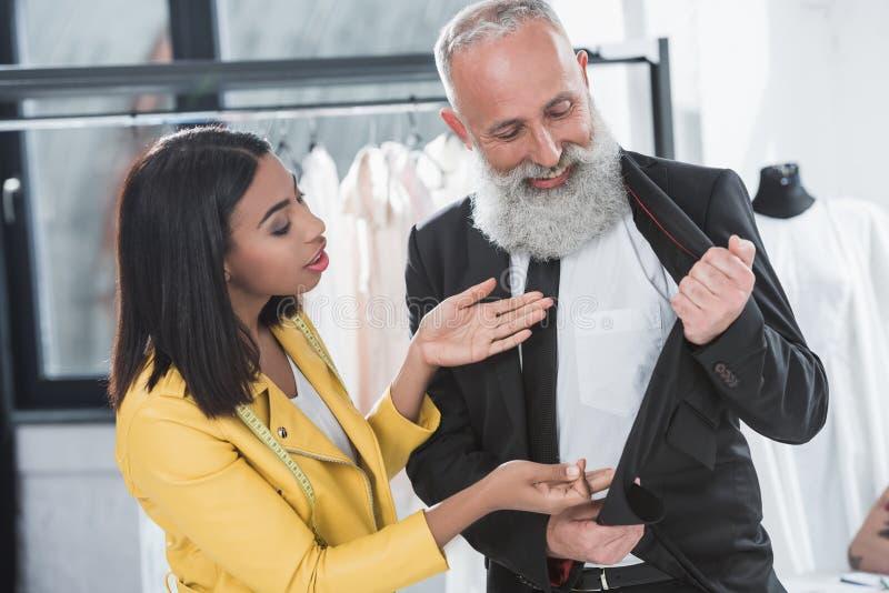 Stylista opowiada z popielatym z włosami klientem w kostiumu indoors fotografia stock
