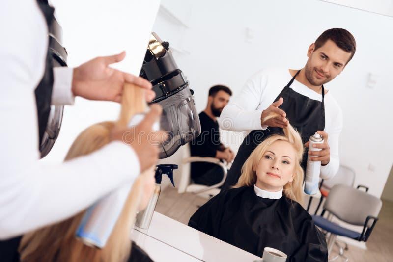 Stylista stosuje lakier do włosów na blondynie patrzeje w lustrze dojrzała kobieta zdjęcie royalty free