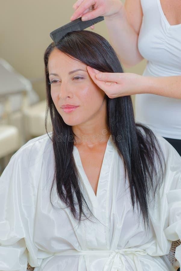 Stylista szczotkuje klienta ` s włosy obrazy royalty free