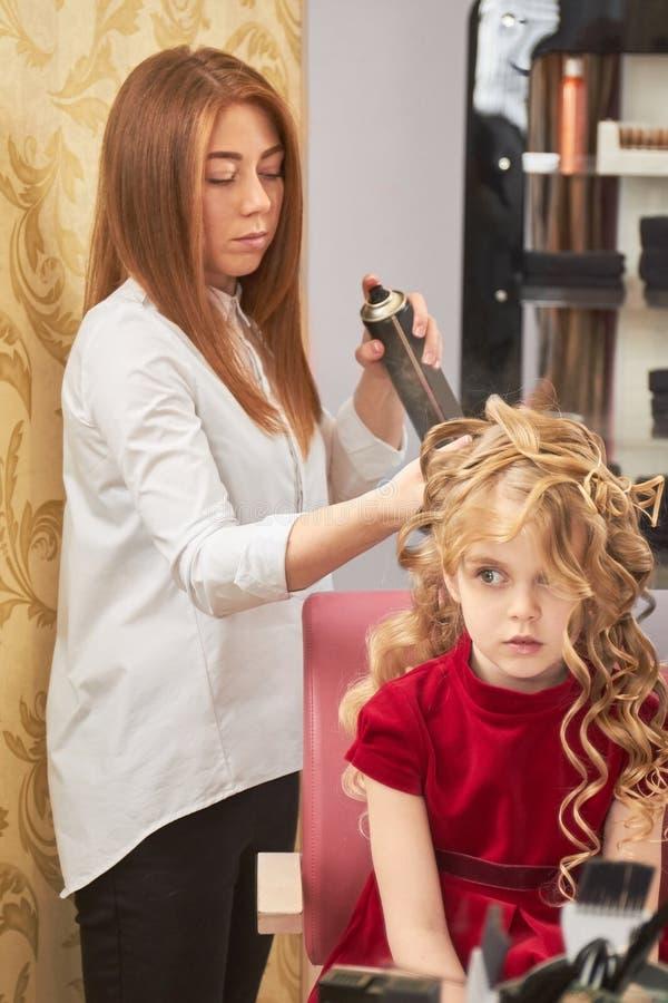 Stylista używa lakier do włosów, mała dziewczynka zdjęcia stock