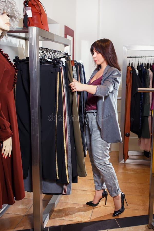 Stylista wybiera odzieżowego w sklepie fotografia stock