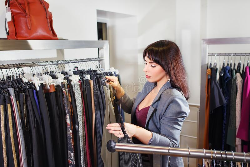Stylista wybiera odzieżowego w sklepie obraz stock