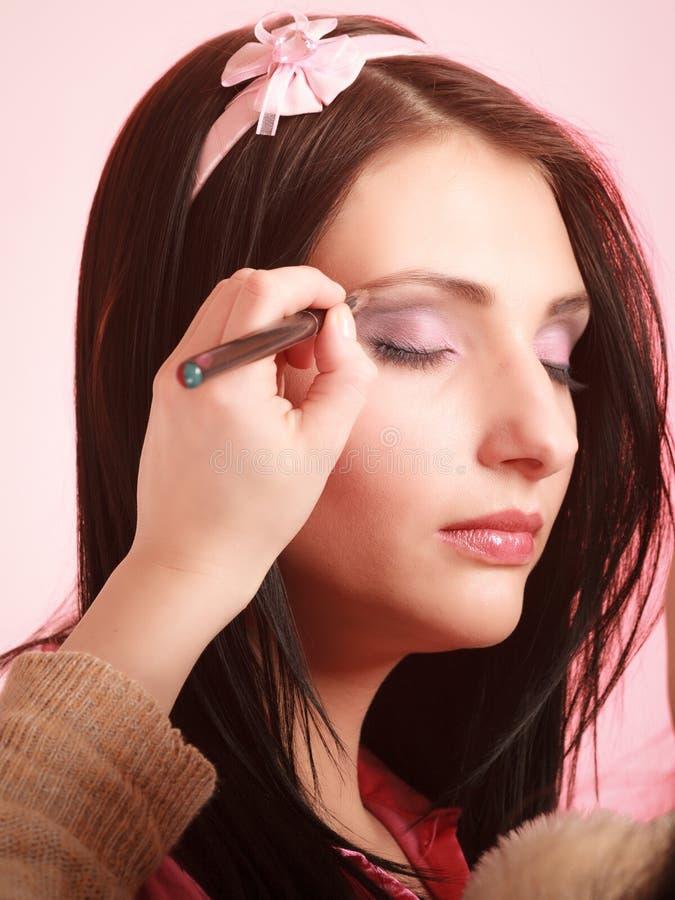 Styliste de maquilleur appliquant le fard à paupières sur la paupière de la femme photo stock