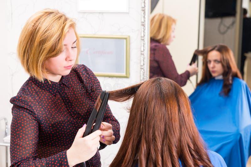 Styliste employant le fer plat pour dénommer des cheveux de clients images stock