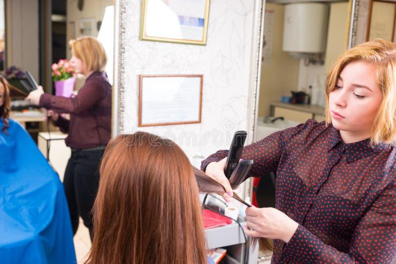 Styliste employant le fer plat sur des cheveux de client de brune images stock