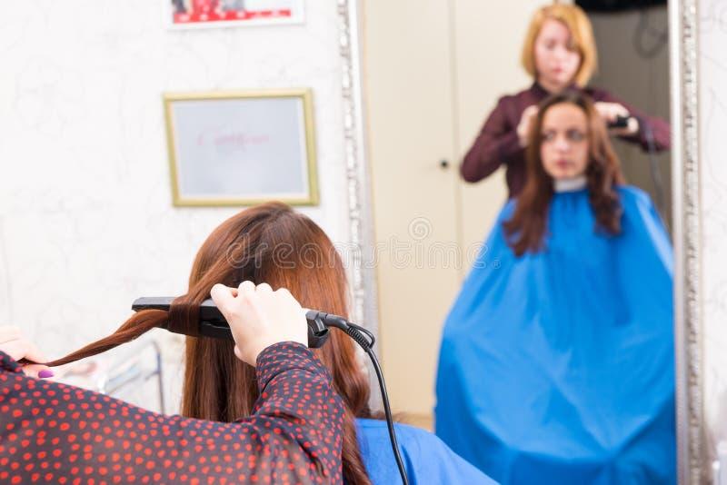 Styliste employant le fer plat sur des cheveux de client de brune image libre de droits