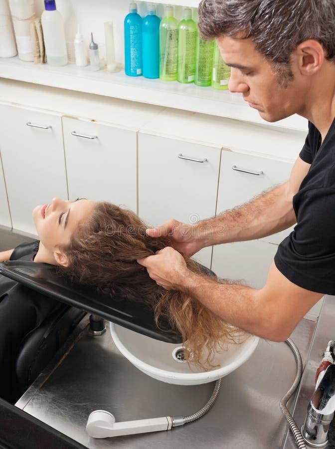 Styliste en coiffure avec le client se préparant au lavage de cheveux images libres de droits