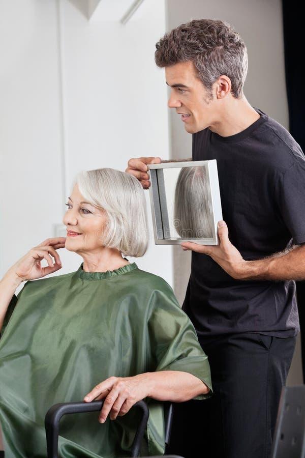 Styliste en coiffure montrant la coupe de cheveux de finition au client photos libres de droits