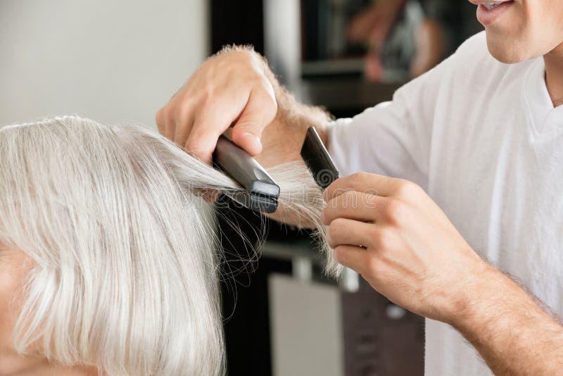 Styliste en coiffure redressant les cheveux de la femme photo libre de droits