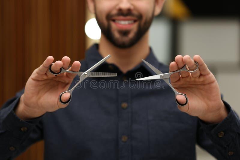 Styliste en coiffure tenant des ciseaux professionnels dans le salon de beauté image stock