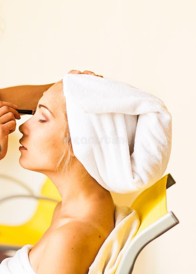 Styliste s'appliquant le maquillage à la jeune belle femme images stock