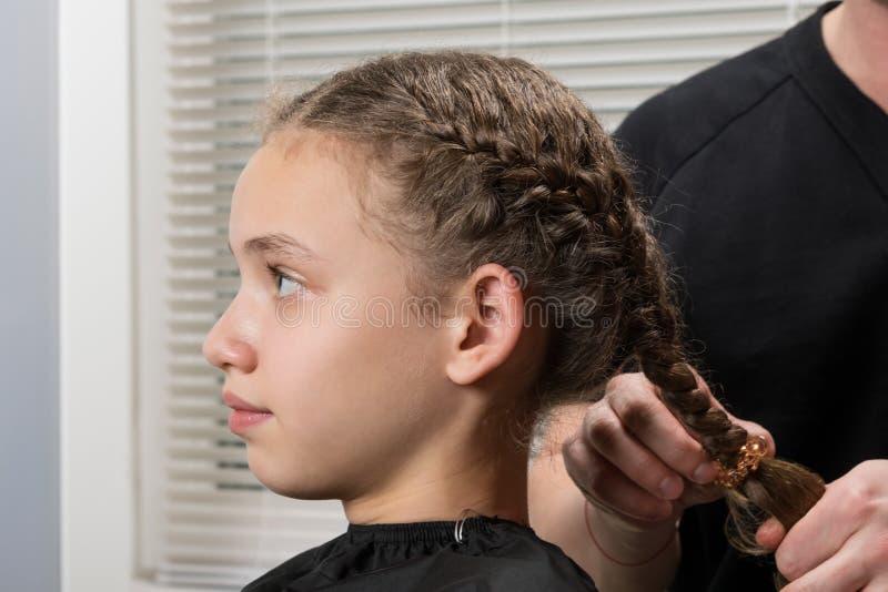 Stylisten gör flickan en flätad tråd för hår, närbild royaltyfri foto