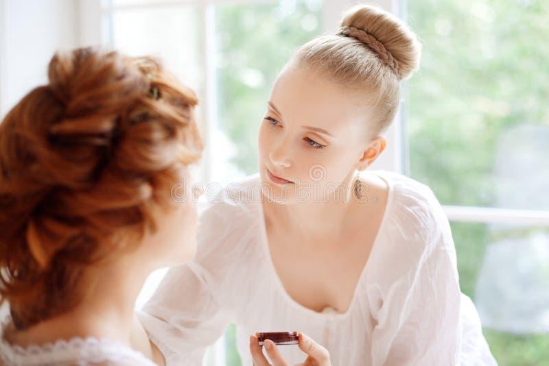 Stylisten gör makeupbruden för bröllopet arkivfoto
