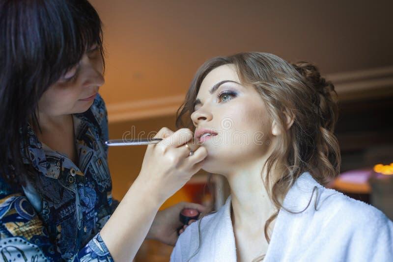 Stylisten gör makeupkvinnan på bröllopdag fotografering för bildbyråer
