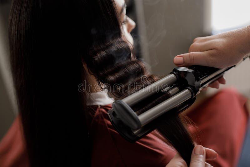 Stylisten gör permed lås för kvinna royaltyfri fotografi