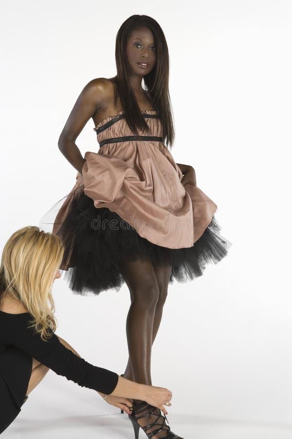 Stylistes de mode ajustant les chaussures du modèle image stock