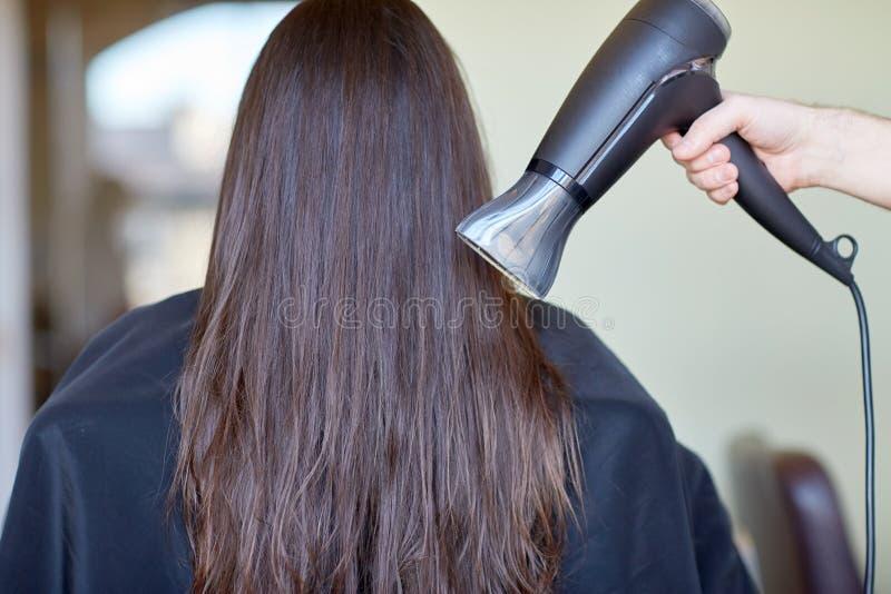 Stylisthanden med fanen torkar kvinnahår på salongen royaltyfri bild