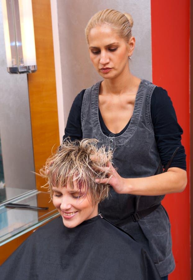 stylistkvinna för torkande hår arkivbild