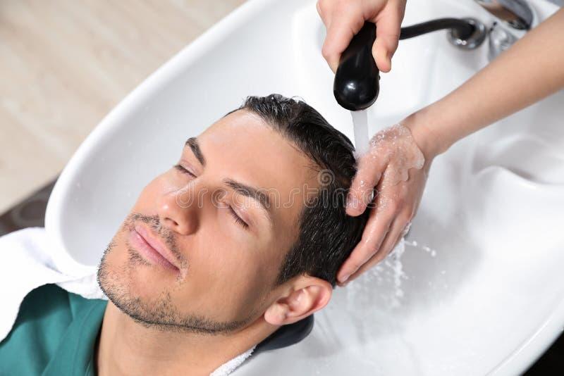 Stylisttvagningklients hår på vasken royaltyfria bilder