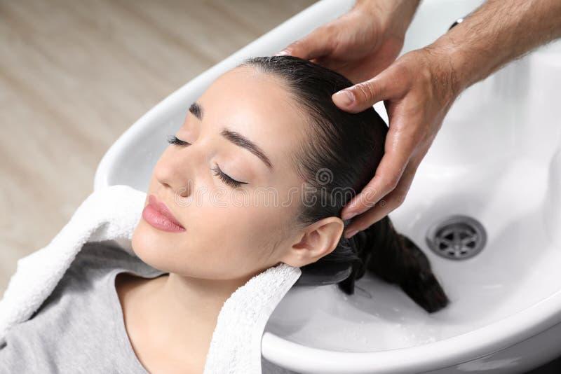 Stylisttvagningklients hår på vasken arkivfoton