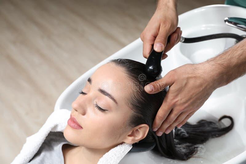Stylisttvagningklients hår på vasken i skönhetsalong royaltyfri bild