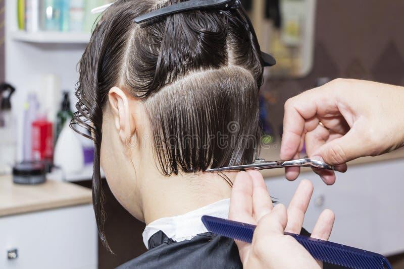 Stylisty fryzjer w fryzjera męskiego sklepie robi ostrzyżenia zbliżeniu obrazy stock