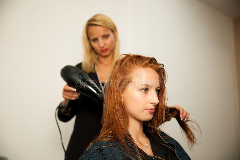 Stylisty suszarniczy włosy żeński klient przy piękno salonem - hai obrazy stock