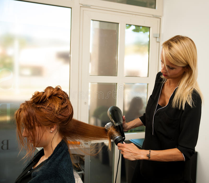 Stylisty suszarniczy włosy żeński klient przy piękno salonem - hai zdjęcie stock