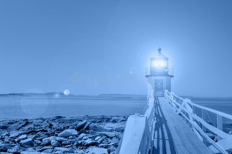 Stylized blue hour image of Marshall Point Lighthouse, Maine, in classic blue 2020 color of the year, symbol of calm, peace, and royalty free stock images