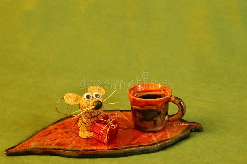 Stylized ceramic stand with mouse made of natural cork, New Year`s gift and clay cup decorated with glaze on green background. royalty free stock photos