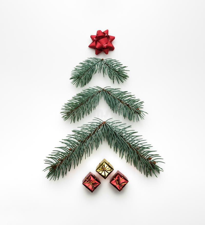 Stylized Christmas tree made of fir branches with gift boxes on white background. Flat lay, view from above royalty free stock images