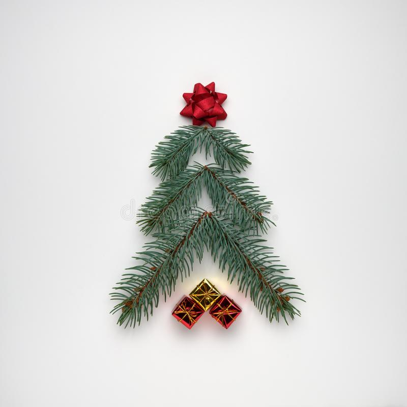 Stylized Christmas tree made of fir branches with gift boxes on white background. View from above, flat lay stock photos