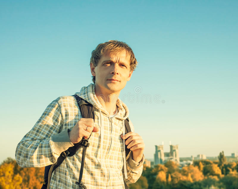 Stylized colorized vintage happy man portrait holding backpack and looking at the sunset royalty free stock photography