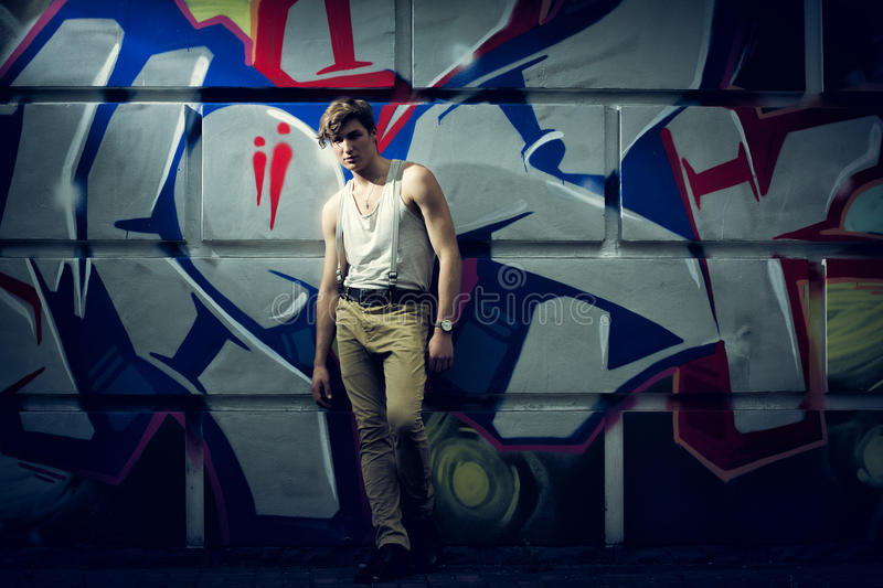 Stylized image of the fashion guy against a wall with graffiti.  royalty free stock image