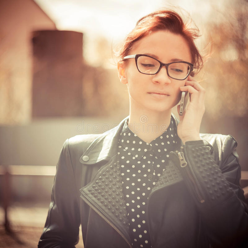Stylized instagram colorized vintage fashion portrait of a young woman wearing glasses with beauty bokeh and small depth of f royalty free stock image