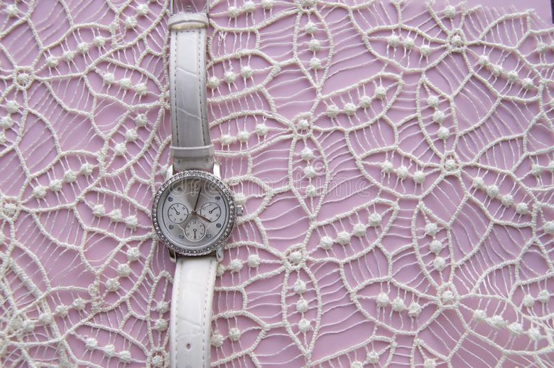 Stylized photo for business women, social networks, women`s posts, modern women`s wristwatch on a noble lace and pink background. Empty space stock images