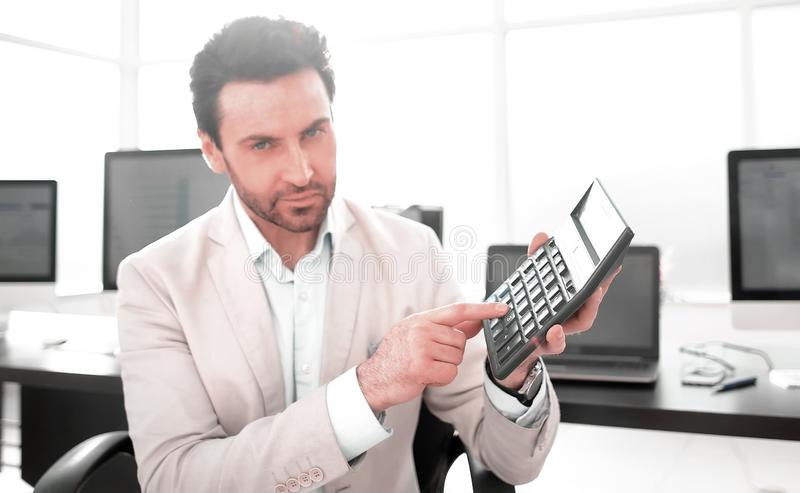 Stylized photo.Businessman pointing to the calculator. Photo with copy space royalty free stock image