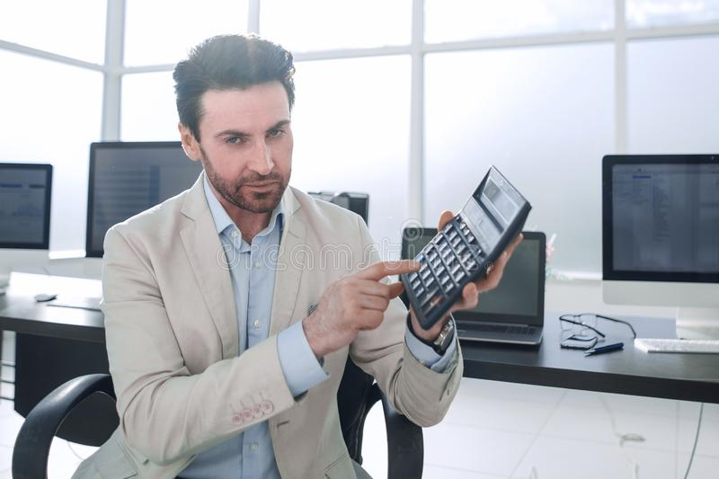 Stylized photo.Businessman pointing to the calculator royalty free stock photography