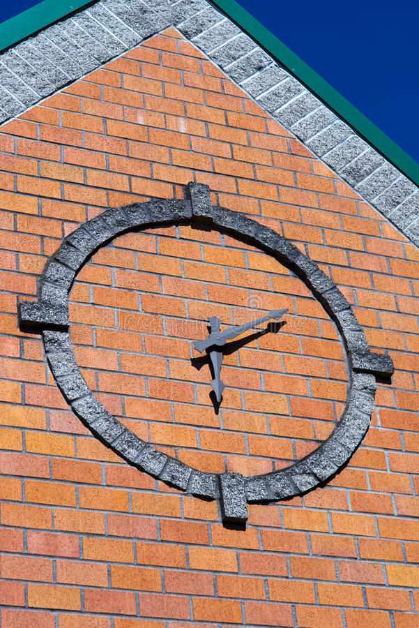 Stylized round clock on brick wall of building façade with coni. These stylized operating clock with arrows in a circle lined with stone blocks on the front stock photo
