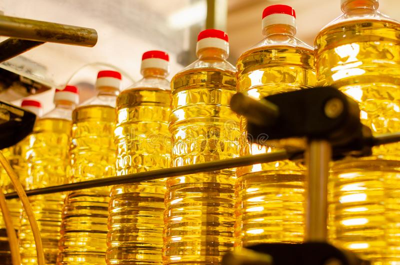 stylized solros för droppe olja Fabrikslinje av produktion och fyllning av förädlad olja från solrosfrö Fabrikstransportör av mat royaltyfria bilder