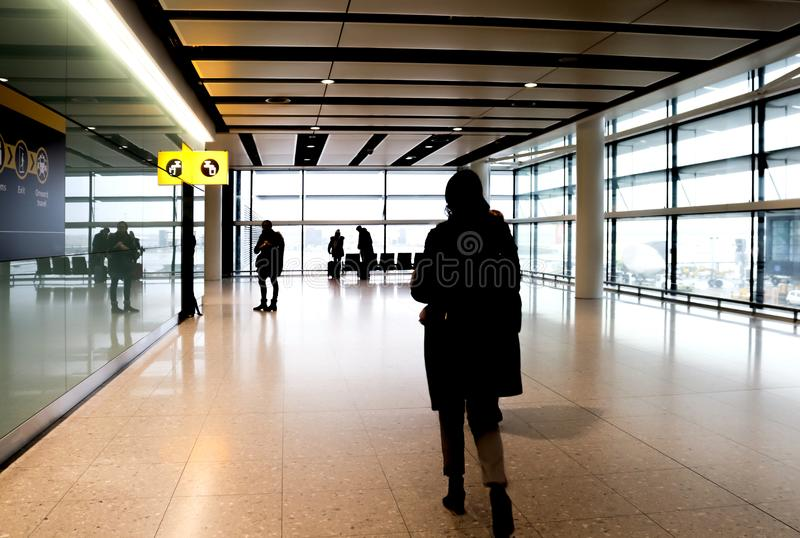 Stylized view of the loney end of a terminal in an airport with the unrecognizable silhouettes of a few bundled up passengers wait stock photos