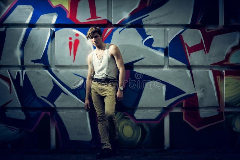 Stylizowany wizerunek moda facet przeciw ścianie z graffiti obraz royalty free