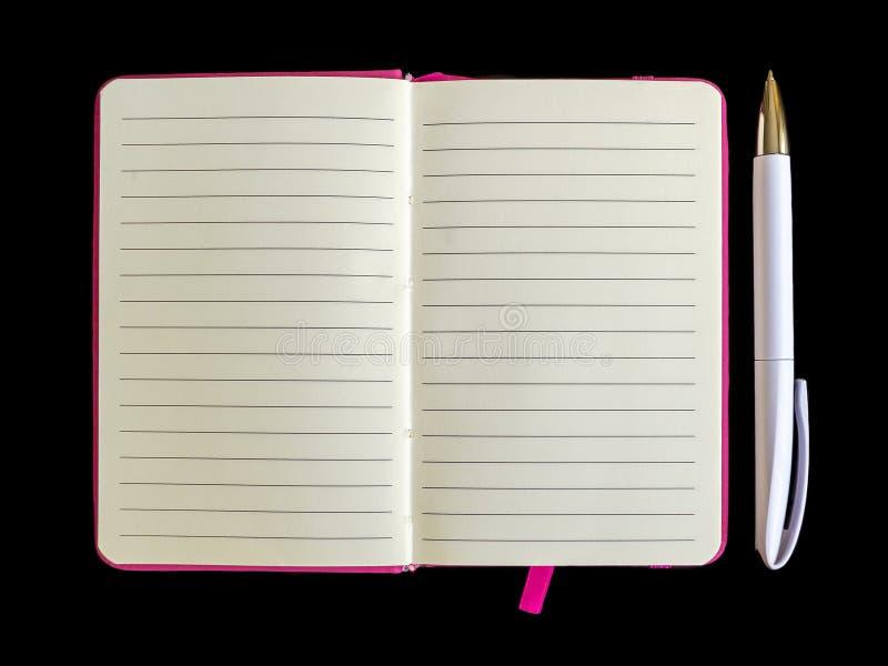 Stylo bille blanc près du carnet ouvert avec le papier rayé dans une couverture rose sur un espace noir de copie de fond image libre de droits
