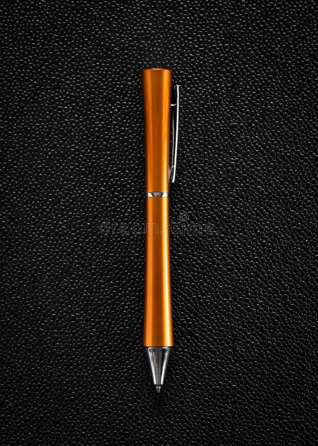 Stylo bille orange sur le fond foncé photographie stock