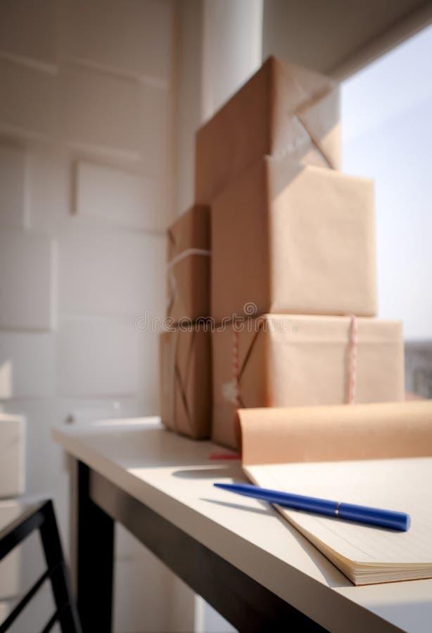 Stylo bleu sur le carnet avec le colis enveloppé sur le bureau blanc photos libres de droits