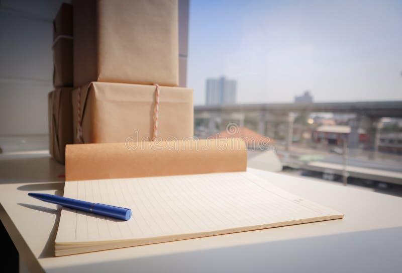 Stylo bleu sur le carnet avec le colis enveloppé sur le bureau blanc photos stock
