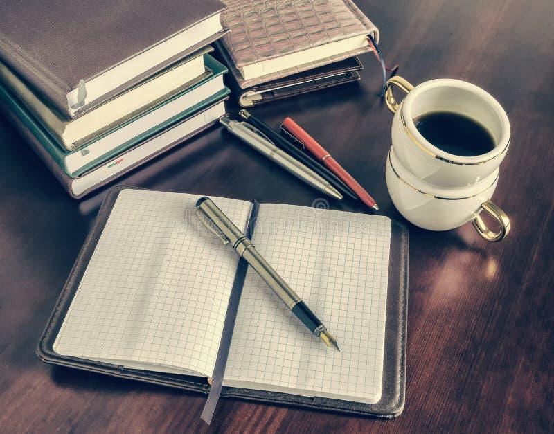 Stylo, carnet ouvert, tasse de café photographie stock libre de droits