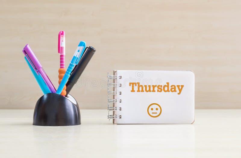 Stylo de couleur de plan rapproché avec le bureau en céramique noir rangé pour le mot de jeudi de stylo et d'orange en page blanc images libres de droits